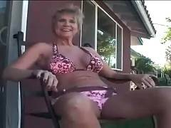 Chubby busty granny is posing naked on back yard.